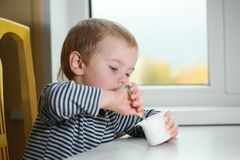 Funny babe blondes licks  finger with yogurt. Funny babe boy blondes licks finger with yogurt Royalty Free Stock Photo