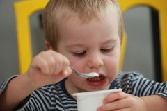 Funny babe blondes licks  finger with yogurt. Funny babe boy blondes licks  finger with yogurt Royalty Free Stock Image