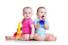 Babies girl and boy play musical toys. Funny babies girl and boy playing musical toys on white background Stock Images