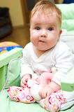 Funny baby. Portrait of a sitting baby girl, making funny face Stock Photography