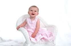 Funny Baby. Baby girl on wicker chair, laughing with funny expression Stock Images