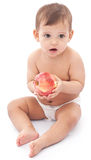 Funny baby with apple sitting on the floor. Royalty Free Stock Photo