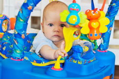 Funny baby   in baby jumper. Funny baby playing in baby jumper Stock Photography