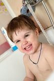 Funny baby bathes in the bath Stock Images