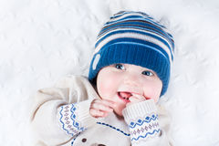 Funny baby in blue knitted hat and warm sweater Royalty Free Stock Image