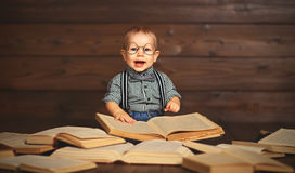 Funny baby with books in glasses stock images