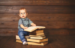 Funny baby with books in glasses. On a wooden background Royalty Free Stock Image