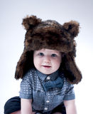 Funny baby boy  in a  brown fur hat . Royalty Free Stock Image