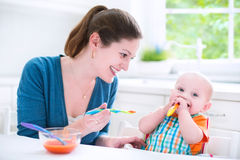 Funny baby boy eating his first solid food with his mother. Young attractive mother feeding her cute baby son, giving him his first solid food, healthy vegetable Stock Photos