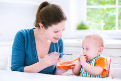 Funny baby boy eating his first solid food. Young attractive mother feeding her cute baby son, giving him his first solid food, healthy vegetable pure from Stock Photo