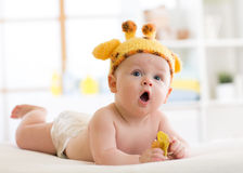 Funny baby boy in giraffe hat lying on his belly in nursery. Little kid lies on bed with opened mouth and holds soother. Baby boy in a funny giraffe hat lying on Royalty Free Stock Images