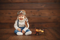 Funny baby boy pilot aviator with airplane laughing Stock Photography