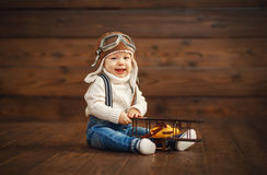 Funny baby boy pilot aviator with airplane laughing Royalty Free Stock Images