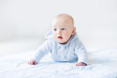 Funny baby boy playing on a bue blanket Royalty Free Stock Images