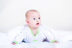 Funny baby boy playing under a white blanket. Wearing a green shi Royalty Free Stock Photos