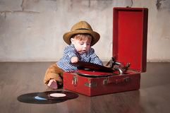 Funny baby boy in retro hat with vinyl record and gramophone.  Royalty Free Stock Image