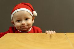 Funny baby boy in santa hat hold the table royalty free stock photo