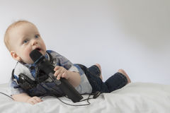 Funny baby boy singing karaoke. Lying infant kid with microphone and headphones. Concept for advertising of karaoke club royalty free stock image