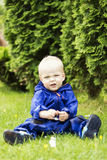 Funny baby boy sitting on the grass in a blue raincoat. Cute infant kid playing on the backyard.  Royalty Free Stock Photos
