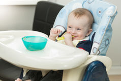 Funny baby boy sitting in highchair and playing with spoon and d. Portrait of funny baby boy sitting in highchair and playing with spoon and dish Stock Image