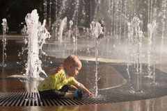 Funny baby boy splashing in fountain. Cute toddler playing with water stream Royalty Free Stock Photography