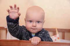 Funny baby standing in a crib holding up his hand stock photos