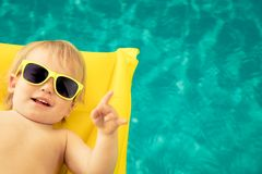 Funny baby boy in swimming pool stock image