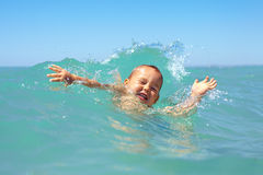 Funny baby boy swimming in waves Royalty Free Stock Photography