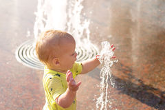 Funny baby boy trying to cauch water stream in fountain. Cute toddler playing in the city fountain Stock Image