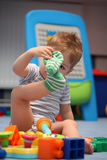 A funny baby boy trying to dress socks Stock Photo