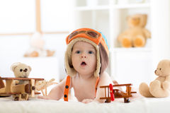 Funny baby boy weared pilot hat with wooden airplane and teddy bear toys Royalty Free Stock Photo