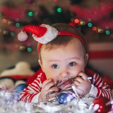 Beautiful little baby boy in Santa hat celebrates Christmas and play with garland. New Year`s holidays. Toddler with gift in the Royalty Free Stock Photo