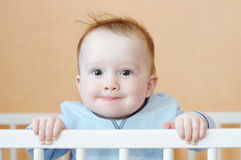 Funny baby boy in white bed Stock Photos