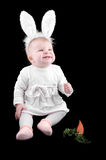 Funny baby in bunny costume and carrot Stock Images