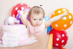 Funny baby celebrating first birthday. Cake. Funny baby celebrating first birthday. Cake is surprise for child. Many balloons! Decoration at home. Make a first Stock Image