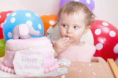 Funny baby celebrating first birthday and eating cake. Stock Photos