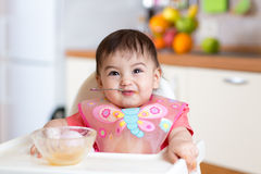 Funny baby child eating itself with spoon in kitchen Royalty Free Stock Photos