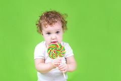 Funny baby with a colorful candy on green background Stock Image