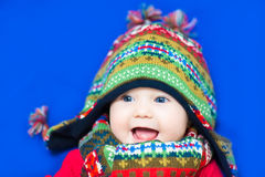 Funny baby in a colorful knitted hat on blue background Royalty Free Stock Photos
