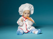 Funny baby with cook costume holds carrot Royalty Free Stock Photos