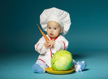 Funny baby with cook costume holds carrot Stock Image
