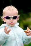Funny baby with cookies. Funny blond baby in sunglasses with cookies royalty free stock images