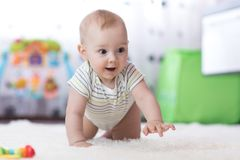 Funny baby crawling on floor at home stock image