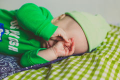 Funny baby crying. Funny baby boy in green t-shirt crying and close his eyes with his hands Stock Image