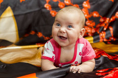 Funny baby on a dark background. Laughing baby girl lying on her stomach in bed dark color Stock Photos