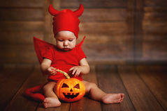 Funny baby in devil halloween costume with pumpkin Stock Image