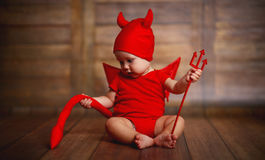 Funny baby in devil halloween costume on wooden background stock photo