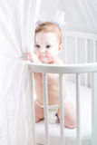 Funny baby in a diaper playing in its crib. Funny little baby in a diaper playing in its crib Royalty Free Stock Photography