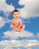 Funny baby in diaper sitting on a cloud Royalty Free Stock Image