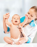 Funny baby and doctor pediatrician. doctor listens to the heart Royalty Free Stock Photos